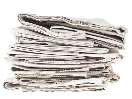 untidy pile of old folding newpapers on white background