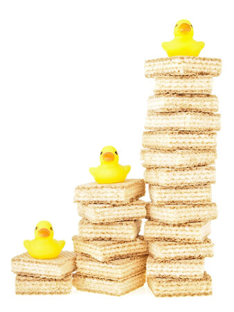 duckie: step of untidy stack wafer increase with duck toy on top on white background
