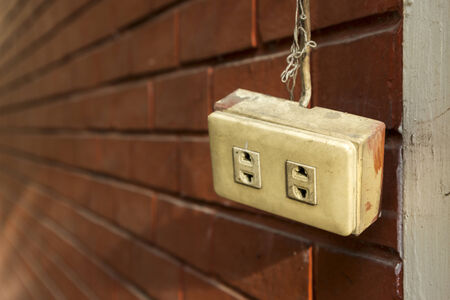 perspective of hanging old plug socket in front of brick wall photo