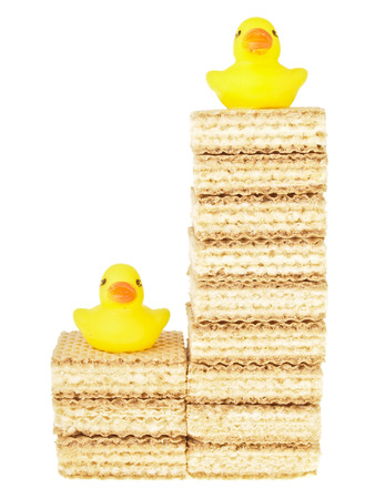 duckie: high - low lever of wafer stack with duck toy on top on white background