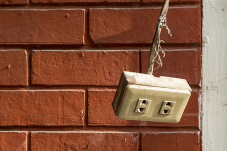 hanging of old plug socket on red brick wall in sunlight