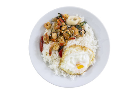 dish of rice topped with stir-fried pork and basil and fried egg on white background. this menu is thai food and popular in Thailand.