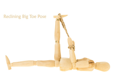 demonstration of wood manikin in reclining big toe pose on white background. this pose is part of yoga training.