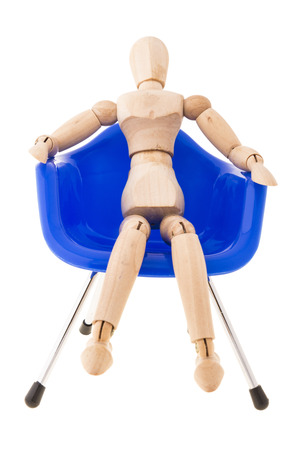 pose of wood figure comfortable sit on blue plastic chair on white background photo