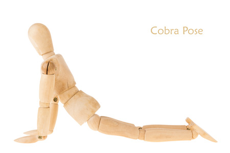 demonstration of wood manikin in cobra pose on white background. this pose is part of yoga training. Stock Photo