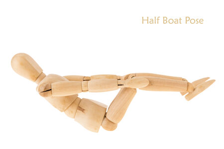 limber: demonstration of wood manikin in half boat pose on white background. this pose is part of yoga training. Stock Photo