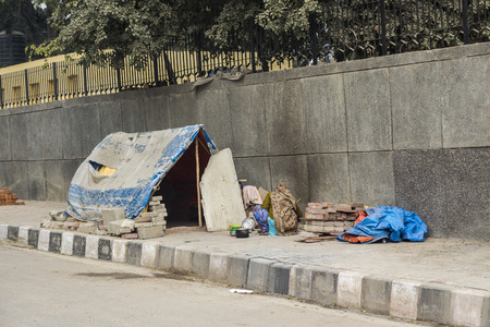 poverty india: comporary tent of unidentified homeless people on side of street in Delhi, India