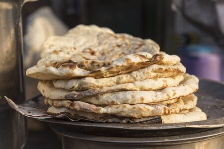 roti pile in street food stall in marketplace of Delhi, India