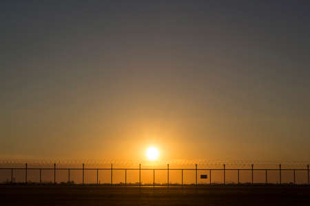 barbed wire frame: scene of sunset behind security barbed wire fence Stock Photo