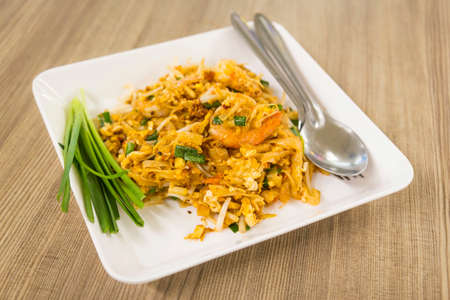 disk of Thai fried noodle with prawn on wooden table Stock Photo