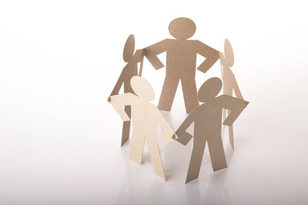 circle joining of five paper figure in standing akimbo posture on white background Stock Photo