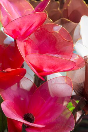 close up of red crafts floral decoration in sunlight