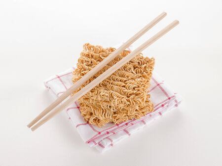 uncooked: top view of double raw instant noodle on dish towel with chopsticks on white background