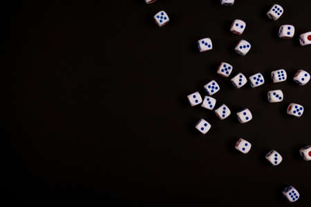 background of pitching many white dice on black paper, concept for business risk, chance, good luck or gambling
