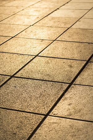 golden sunlight on square pavement, shadow depth of field.