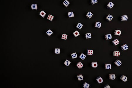 many dice fall spread on black paper background, concept for business risk, chance, good luck or gambling