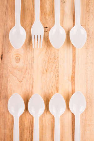 white plastic fork in spoon border decoration on wooden background