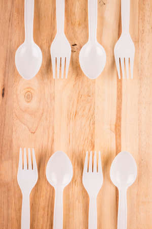 plastic spoon and fork set border decoration on wooden background