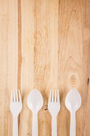 plastic spoon and fork set array decoration on wooden background
