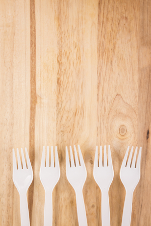 white plastic fork array decoration on wooden background
