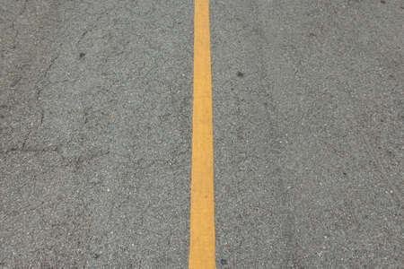 background of yellow solid line on gray roadway