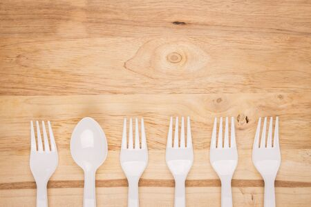 wooden background of white plastic spoon in fork line decoration Stock Photo
