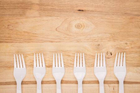 wooden background of white plastic fork array decoration