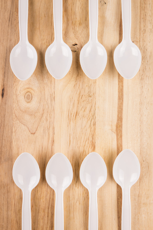 white plastic spoon border decoration on wooden background Stock Photo