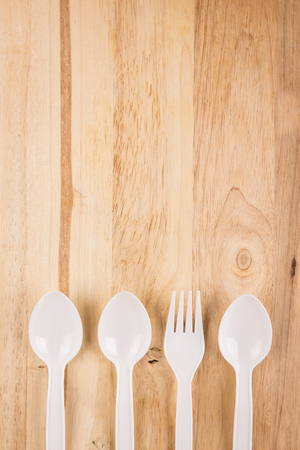 white plastic fork in spoon array decoration on wooden background