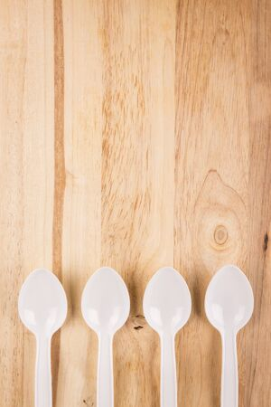 white plastic spoon array decoration on wooden background