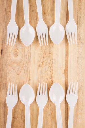 white plastic spoon and fork set border decoration on wooden background