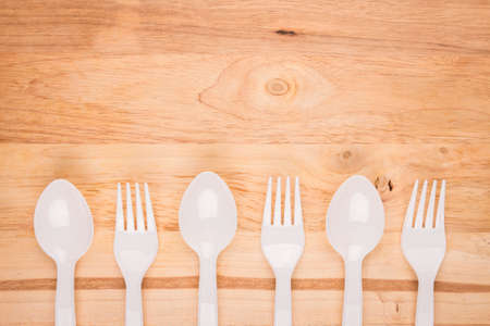 wooden background of white plastic spoon and fork set decoration