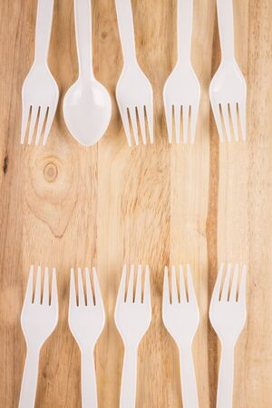 white plastic spoon in fork border decoration on wooden background Stock Photo