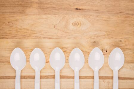 wooden background of white plastic spoon array decoration