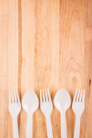 white plastic spoon and fork set array decoration on wooden background Stock Photo