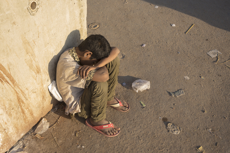 DELHI INDIA-MAR 24 : unidentified homeless boy sit on street in morning sunlight in old delhi of Delhi on march, 24, 2015, india.