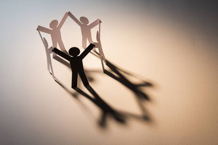 black figure in closed joining of five white paper figure in hand up posture on white background. in concept of business, cooperation and weakness.