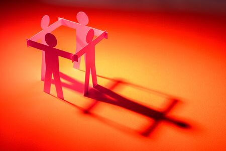 closed joining of four  paper figure on red light background. in concept of business, cooperation and critical.