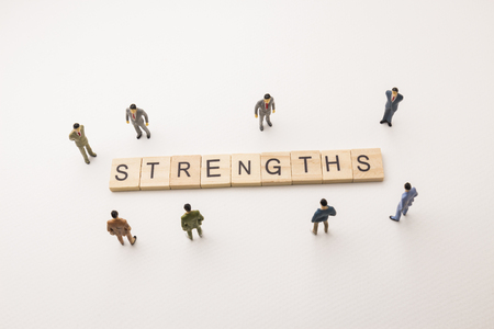 Miniature figures businessman : meeting on strengths letters by wooden block word on white paper background, in concept of business and corporation