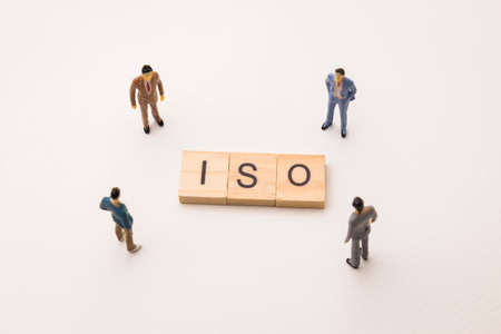 Miniature figures businessman : meeting on iso letters by wooden block word on white paper background, in concept of business and corporation