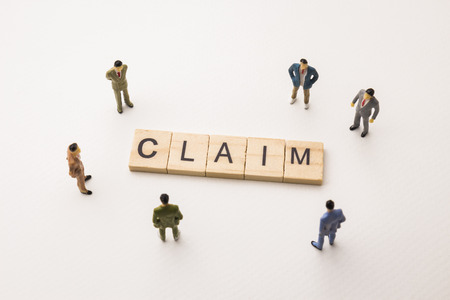 Miniature figures businessman : meeting on claim letters by wooden block word on white paper background, in concept of business and corporation