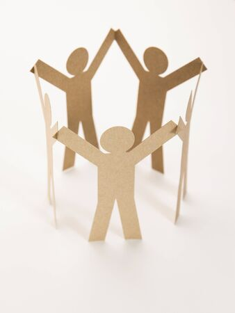 close up of closed joining of five brown paper figure in hand up posture on white background. in concept of cooperation and teamwork Stock Photo