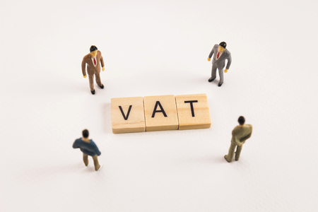 Miniature figures businessman : meeting on vat letters by wooden block word on white paper background, vat is acronym from word Value Added Tax.