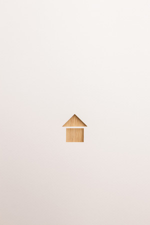 paper cutout in basic house shape by brown wooden textured on white paper background, for home and insurance conceptual.