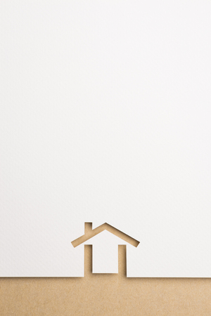 white paper cutout in minimal house shape with border background by brown paper, for home and insurance conceptual. Banco de Imagens