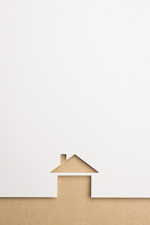 white paper cutout in basic house shape with border background by brown paper, for home and insurance conceptual. Banco de Imagens