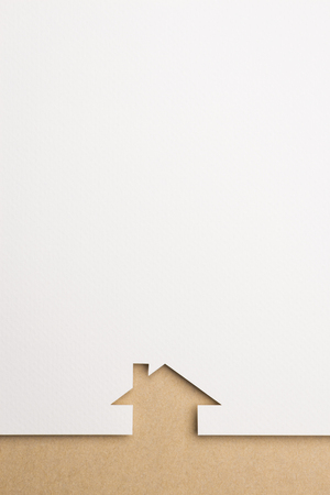 white paper cutout in simple house shape with border background by brown paper, for home and insurance conceptual. Stock Photo