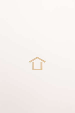 paper cutout in minimal house shape by white textured plate on white paper background, for home and insurance conceptual.