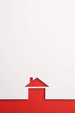 white paper cutout in basic house shape with border background by red paper, for home and insurance conceptual. Banco de Imagens