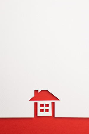 white paper cutout in complete house shape with border background by red paper, for home and insurance conceptual.